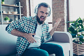 Attractive, bearded man sitting on the couch in living room, having headphones on his head, listening his favorite music, singing a song dreaming like playing guitar