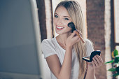 Attractive beautiful charming joyful glad woman wearing white t-shirt is applying blusher on her cheekbones in front of mirror at home