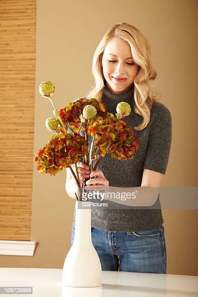 Attraktiven blonden Frau arrangieren Blumen in einer Vase