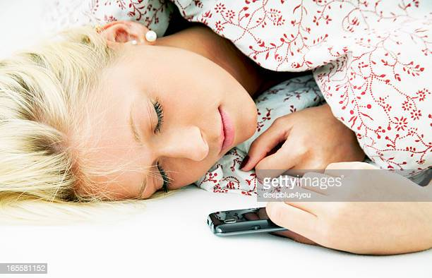 Attractive blond young sleeping woman in bed with smartphone