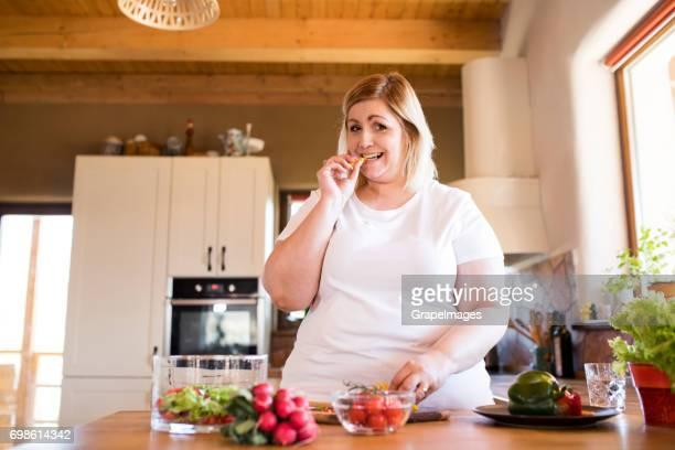 Attraktive blonde übergewichtige Frau in weißem T-shirt zu Hause bereitet einen leckeren gesunden Salat Gemüse in ihrer Küche.