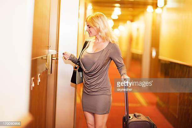Attractive blonde woman opening her hotel room.