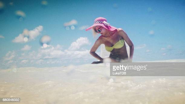 Attractive blonde woman sitting in shallow water, Maldives