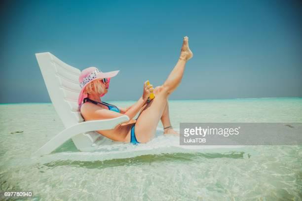 Attraktive blonde Frau sitzt im flachen Wasser, Malediven