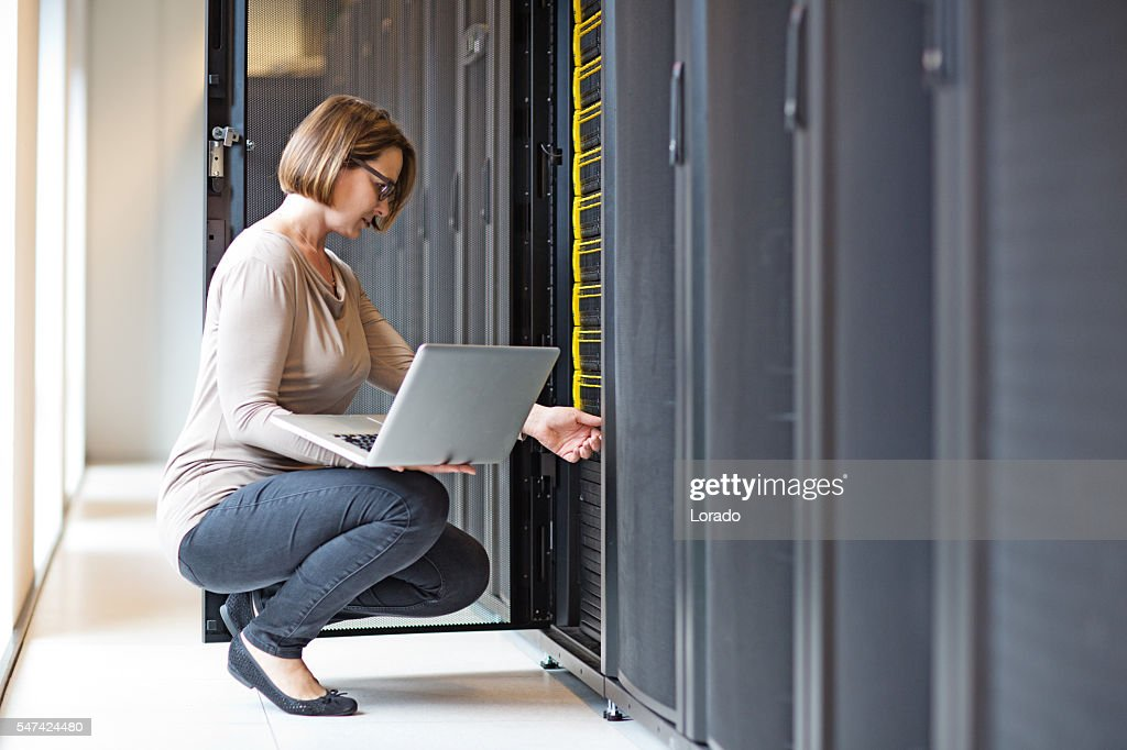 Attractive brunette adult female employee working in internet server room : Stock Photo