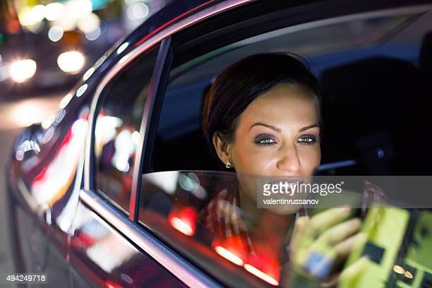 Séduisante brunette envoyer des SMS sur le téléphone dans une voiture