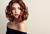 Attractive brown haired  woman  with modern, trendy and elegant hairstyle. Example of middle length,dense and curly hair.Gentle make up and long eyelashes.