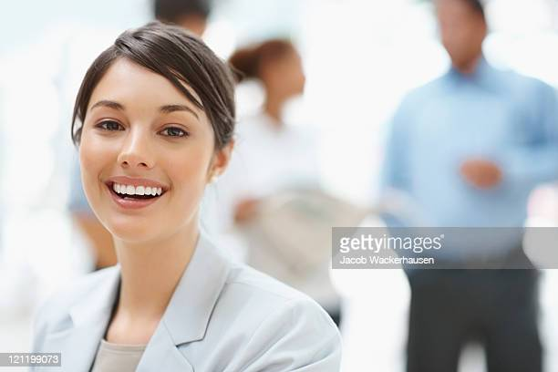 Attractive business lady with colleagues discussing in the back