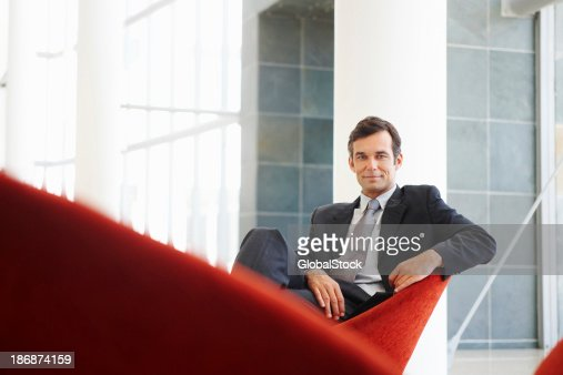 Attractive business man sitting and smiling confidently
