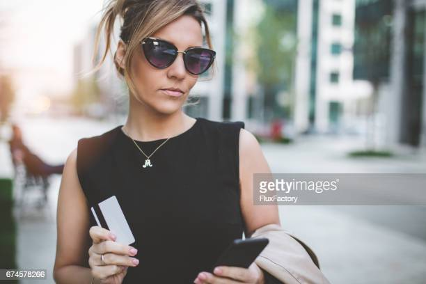 Attractive businesswoman holding phone and credit card