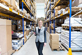 Attractive businesswoman in large warehouse holding tablet