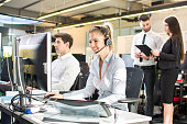 Attractive businesswoman working in call center, surrounded by colleagues.