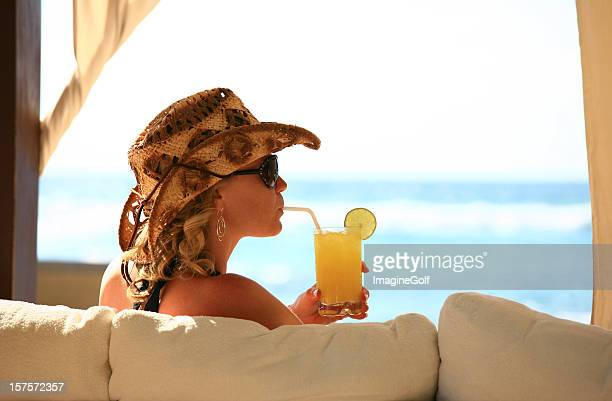 Attractive Caucasian Woman Sipping a Cocktail at the Beach