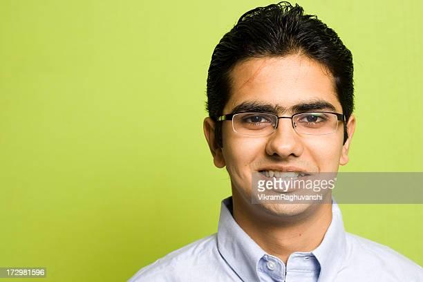 陽気な魅力的な若いインド人男性大人のビジネスマンの緑の背景