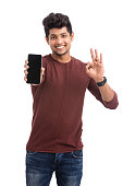 Attractive cheerful young man showing smartphone isolated on white.