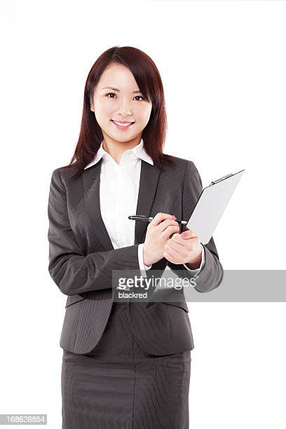 Attractive Chinese Businesswoman Writing on Clipboard Smiling White Background