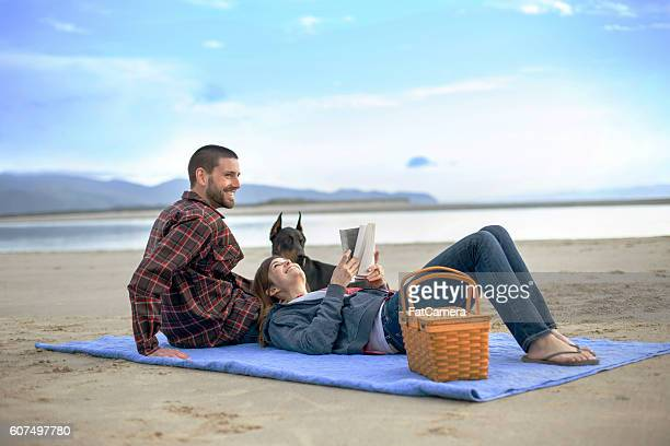 Attractive couple and their dog having a picnic on