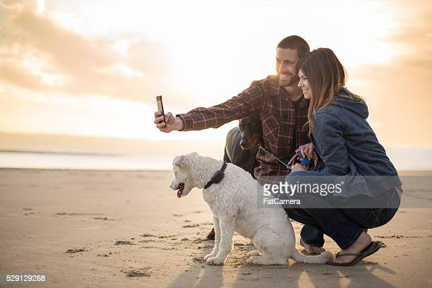 Attractive couple and their dog taking a selfie on