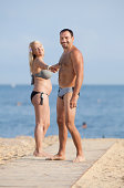 Middle aged man and young pregnant woman on the beach