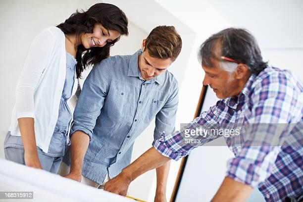 Attrayant couple discuter des travaux de rénovation de maison plan d'architecte