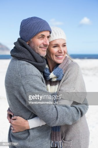 Attractive couple hugging on the beach in warm clothing : Stock Photo