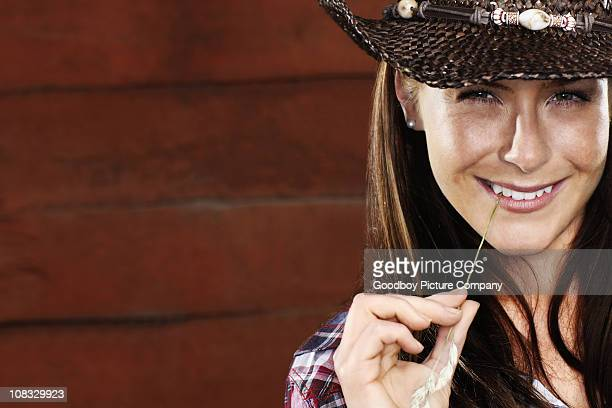 Attractive cowgirl against brown background with copyspace