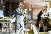 Full length portrait of concentrated young craftswoman in apron standing at spacious workshop and using digital tablet