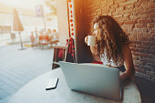 Beautiful curly brunette girl drinks tea or coffee while sitting with portable laptop in street cafe, charming dreamy woman using her computer during rest in cafe with cup of tea