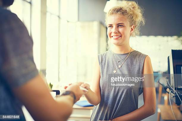 Attractive customer giving card to cashier in cafe