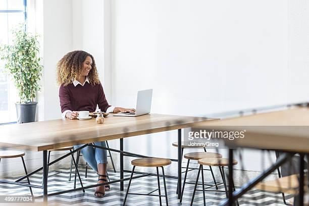 Attraktive ethnische Geschäftsfrau mit laptop in moderne cafe