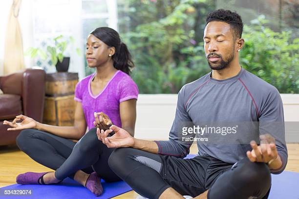 Attractive ethnic couple doing yoga together and meditating