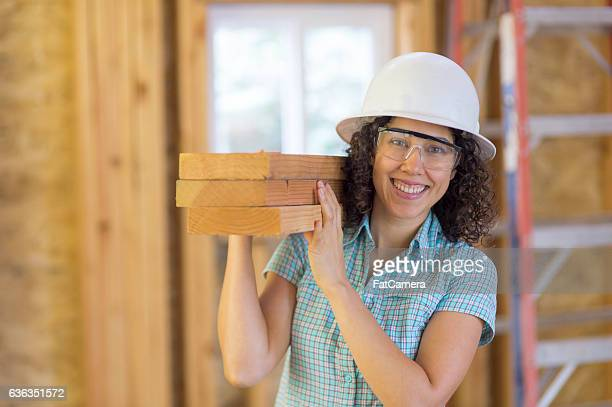 Attractive ethnic female carrying a stack of 2x4's