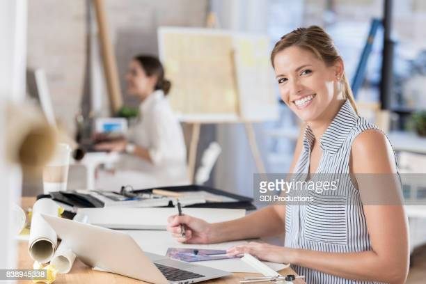 Attractive female architect smiles for camera at work