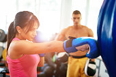 Attractive female athlete practices boxing on punching bag