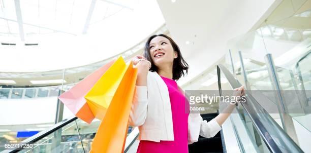 Attractive female shopper standing on escalator