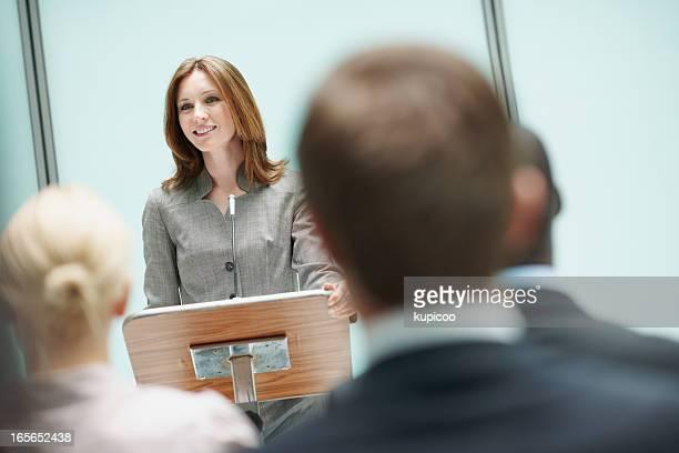 Belle femme avec haut-parleur à séminaire d'affaires