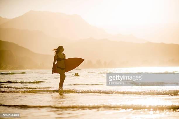 Atractiva mujer surfista en la playa