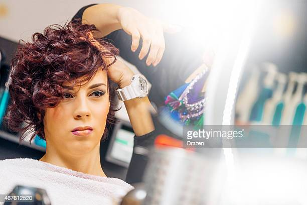 Attractive female with red medium curly hair at hair dresser