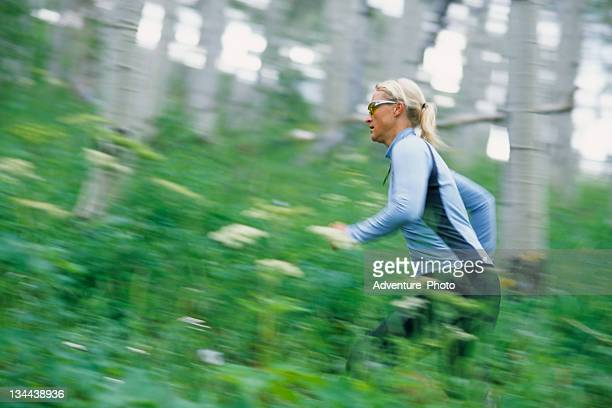 Attractive Fit Young Woman Trail Running in Aspen Forest