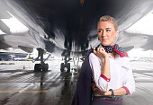 Attractive flight attendant near airplane in airport.