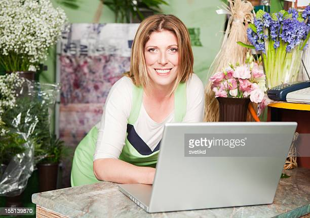 Attractive florist at store using laptop.