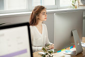 Attractive focused female employee intern working on desktop sitting at coworking space shared office desk, serious young pretty businesswoman worker using pc computer at workplace looking at monitor
