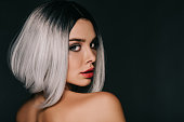 attractive girl posing in grey wig, isolated on black