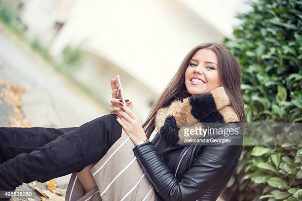 Attraktive Mädchen sitzt auf der Straße in der Stadt und mit Ihrem Smartphone
