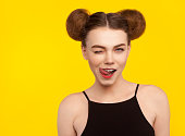 Attractive brunette girl with hair buns winking licking lips wearing black top looking at camera.