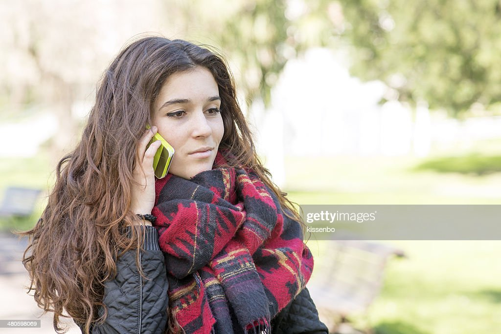 Attractive girl with scarf talking on mobile, outdoor. : Stock Photo