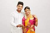Attractive happy south Indian couple in traditional dress, Studio shot.