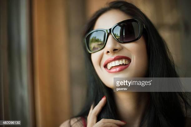 Attraktive, glückliche junge Frau in Sonnenbrille für Offenes Lächeln.