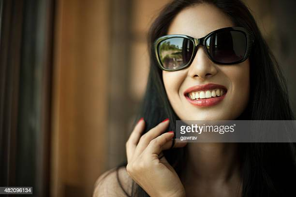 Attractive, happy young woman in sun glasses giving toothy smile.