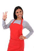 corporate portrait of young attractive hispanic home cook woman in red apron posing happy and smiling giving okay hand sign isolated on white background in chef and successful cooking